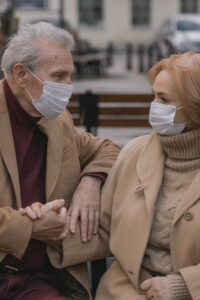 Old man and woman with masks on a bench