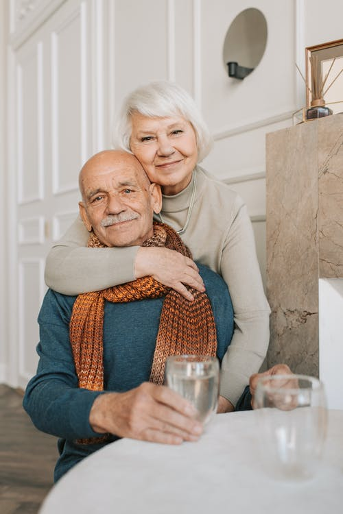 old man and woman hugging